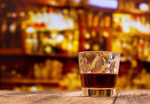 glass of whiskey on wooden table