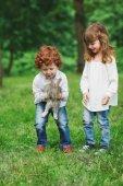 Fotografie Kleine Jungen und Mädchen spielen mit Kaninchen