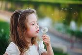 kleines Mädchen mit Löwenzahn im Park