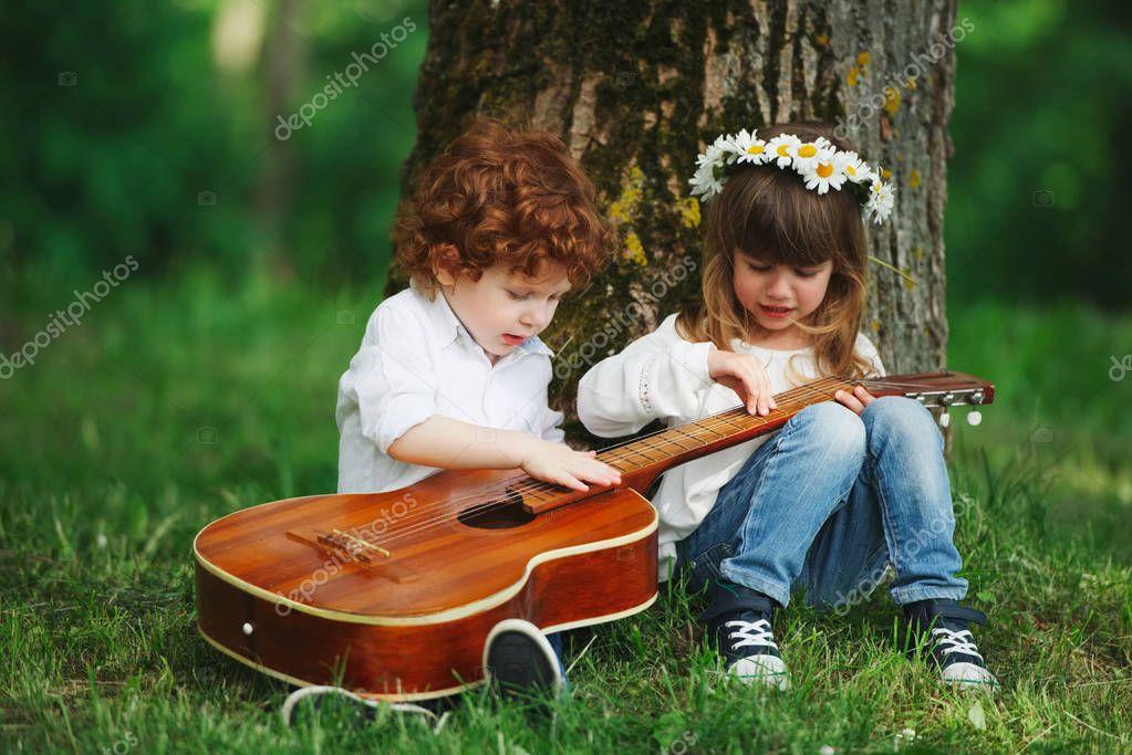 cute little children playing guitar