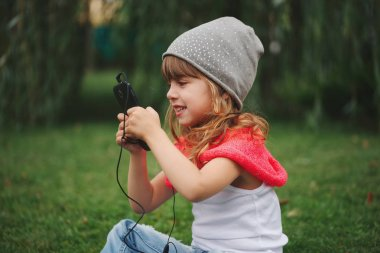 little girl with mobile phone on the grass