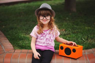 little hipster girl listens music on wireless retro looking spea