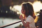 Fotografie kleines Mädchen mit Löwenzahn im park