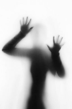 Concept of a frightened woman behind sheet with backlighting in monochrome artistic conversion