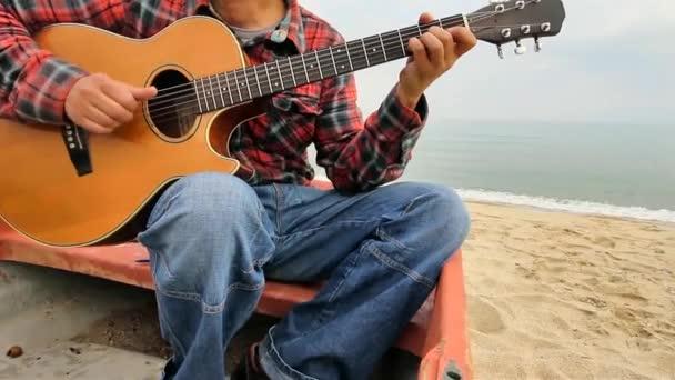 Az ember ül a strandon egy csónakban gitározni