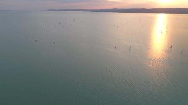 Vitorlás hajók a Balatonon naplementekor