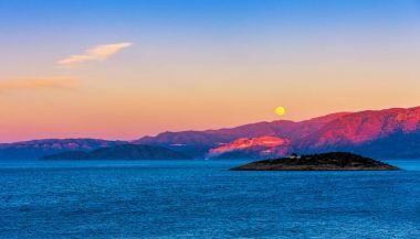 Full moon over Crete at sunset