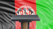 Podium lectern with microphones and Afghan flag in background