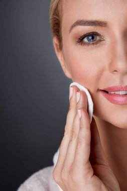 middle-aged woman cleaning skin on face