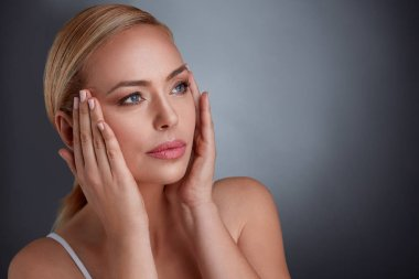 woman tightening skin on face to make you look younger