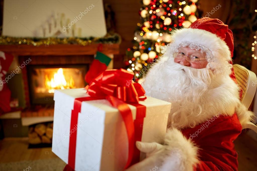 Santa Claus sitzen vor dem Kamin mit großes Geschenk — Stockfoto ...