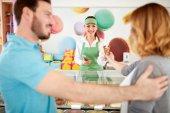 Prodavačka v pekárně dává zmrzlina dívka