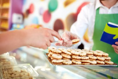 Young shopkeeper at work selling sweets to customer