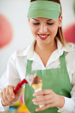 Female vendor in confectionery putting ice cream ball in cone