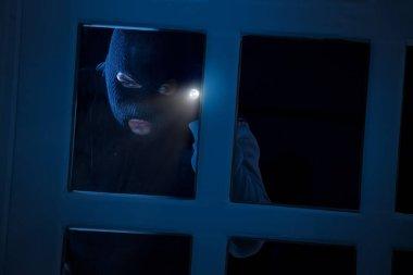 Burglar with flashlight