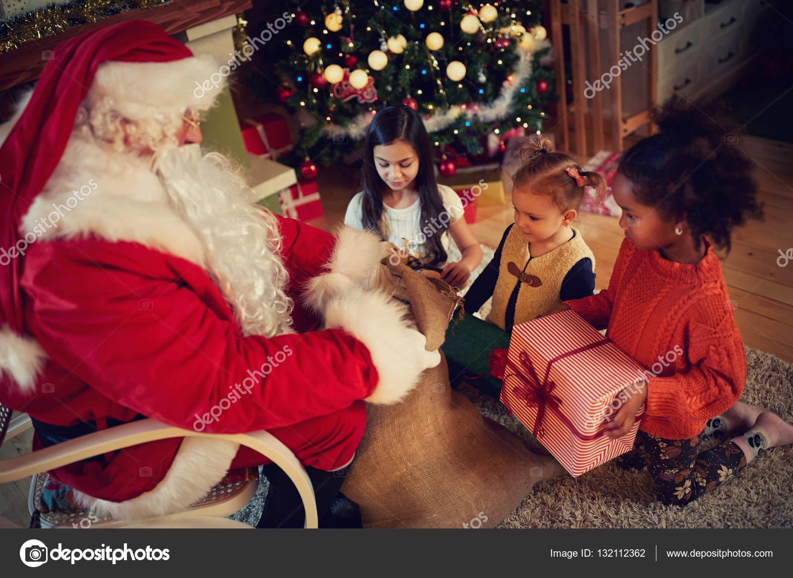 real santa claus gives presents to kids stock photo - Santa Claus Presents