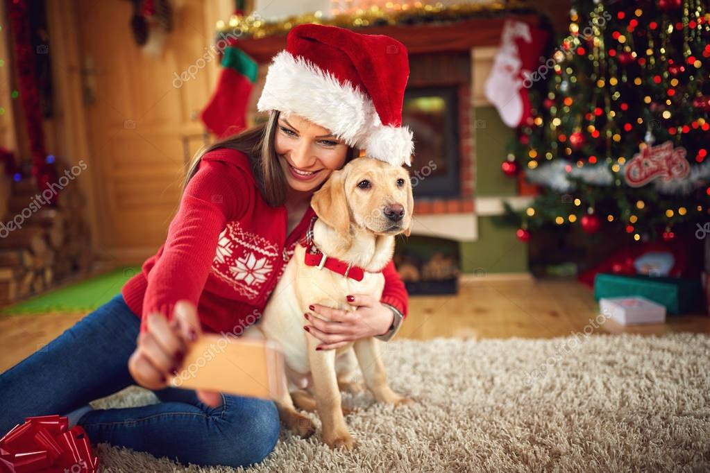 Girl with dog taking Christmas selfie