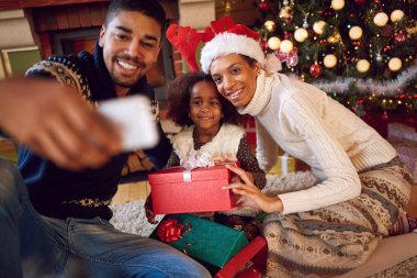 Happy family taking self portrait with smartphone during Christmas