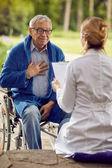 Älterer Mann im Rollstuhl, der sich mit Krankenschwester nicht wohl fühlt