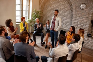 discussion business group- coworkers applauding man in group