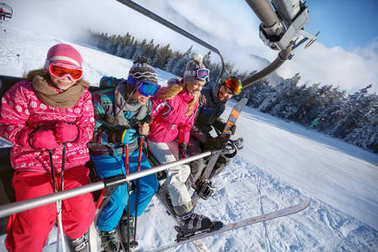 Parents with children in ski lift lifting on ski terrain