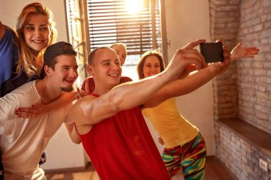 Smiling dancers taking selfie on smartphone while having fun