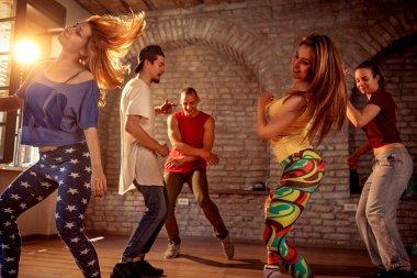 Group of modern street artist break dancers dancing in the studio