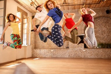 Group of dancers jumping together in dancing studio