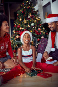 Happy family in front of decorated Christmas tree have fun
