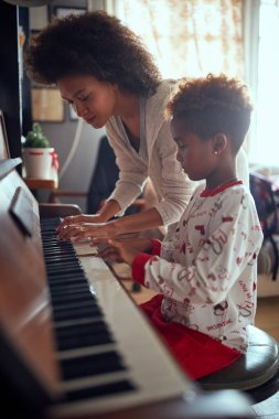 cheerful mother with child girl on Christmas play music on piano