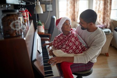 Family on Christmas morning play music on piano.