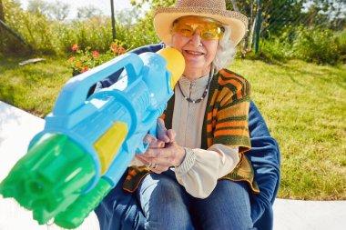 Active Senior woman have fun playing with  water gun.