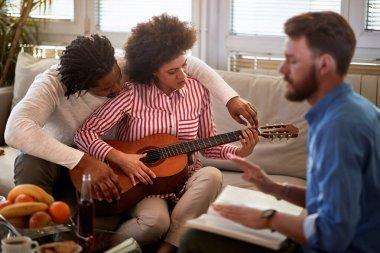 Man teaches woman to play guitar