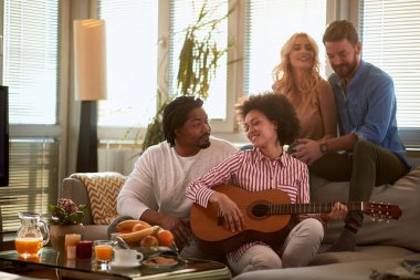 Two couples listening music from guitar