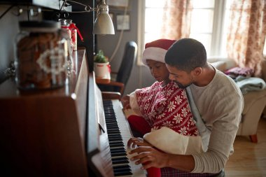 Christmas, winter holidays, new year party and family concept. father  with child  play music on piano.