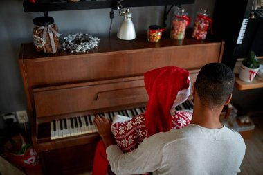 African American Family on Christmas morning play  on piano.