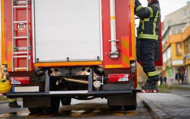 İtfaiye arabasının önündeki üniformalı itfaiyeci kurtarıp koruyacak. Acil durum, tehlike, hizmet kavramı.