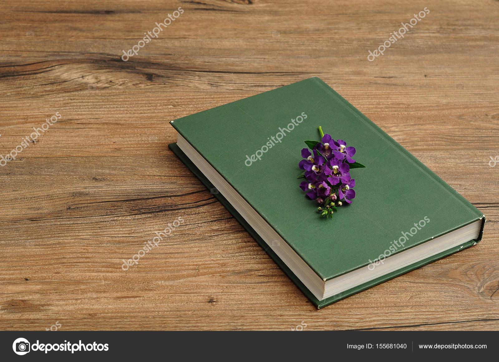 Un libro de cuento tapa dura verde con flores de color púrpura ...