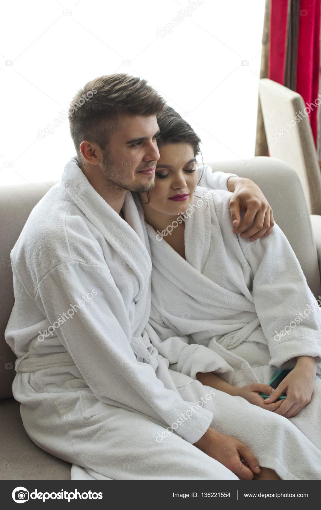 8b28950225137d Casal jovem feliz sentada no sofá no roupão de banho — Stock Photo ...