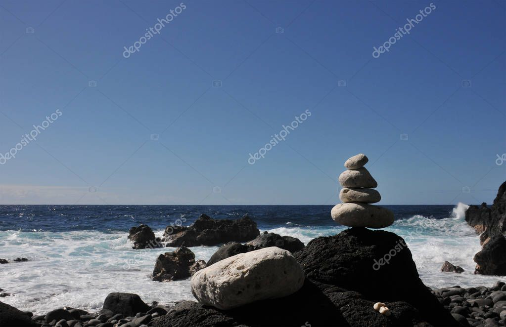 Black Rock with a Pebbles Pile with sea and blue sky