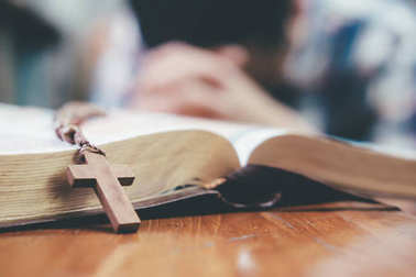 Man praying, hands clasped together on her Bible.