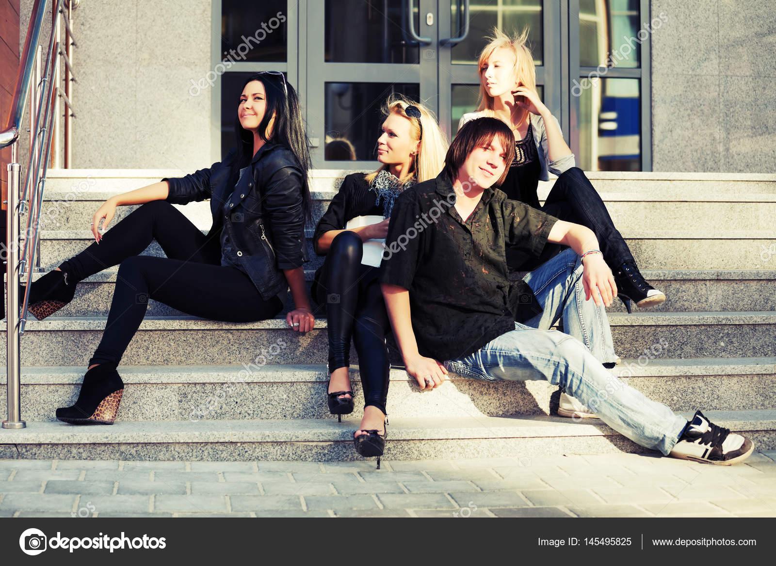 c0395a3116b Móda pro mladé muže a ženy sedí na schodech — Stock Fotografie ...