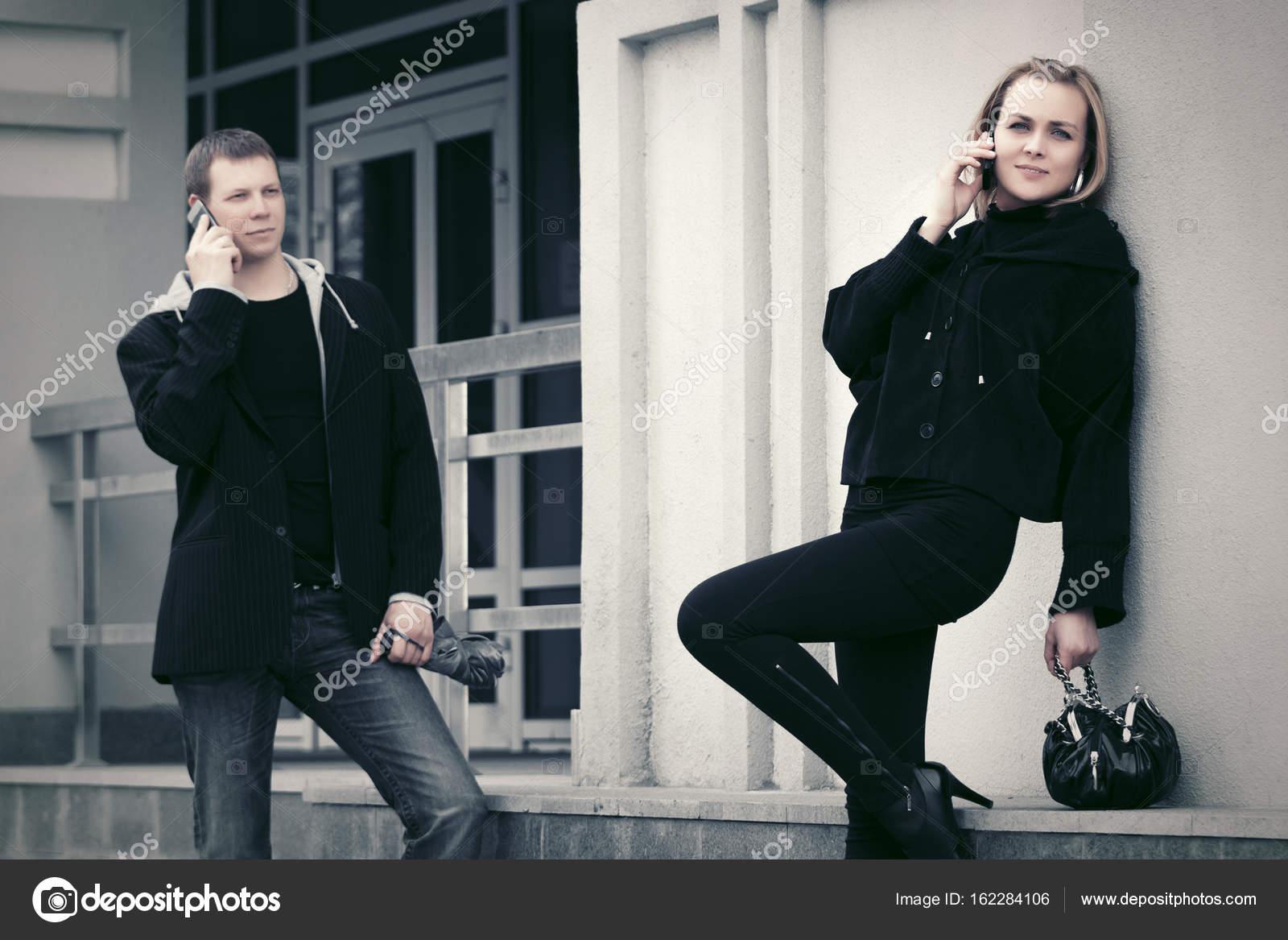 25f9b4be57c2 Mladá móda muž a žena s voláním na mobil outdoor kabelka — Fotografie od ...