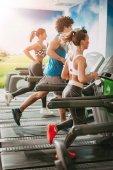 Fotografie Freunde, die laufen auf dem Laufband im Fitnessstudio