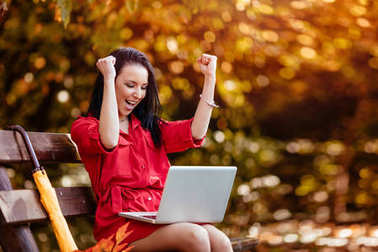 happy woman with laptop sitting on bench