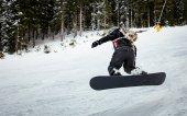 Snowboarder springt über Berghänge und genießt einen gefrorenen Wintertag.