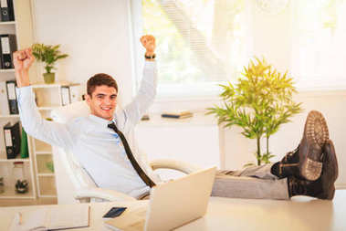Young successful businessman sitting in the office with her feet up on a desk and looking at camera with raised arms. He celebrating good job.