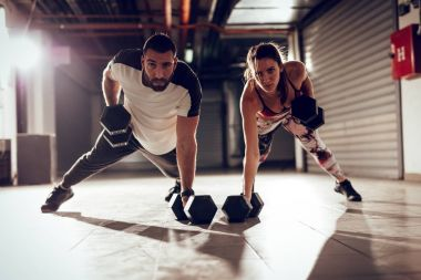 Young muscular couple doing strength exercise on cross fit workout at the garage.