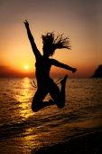 Silueta šťastná dívka skákání při západu slunce na pláži