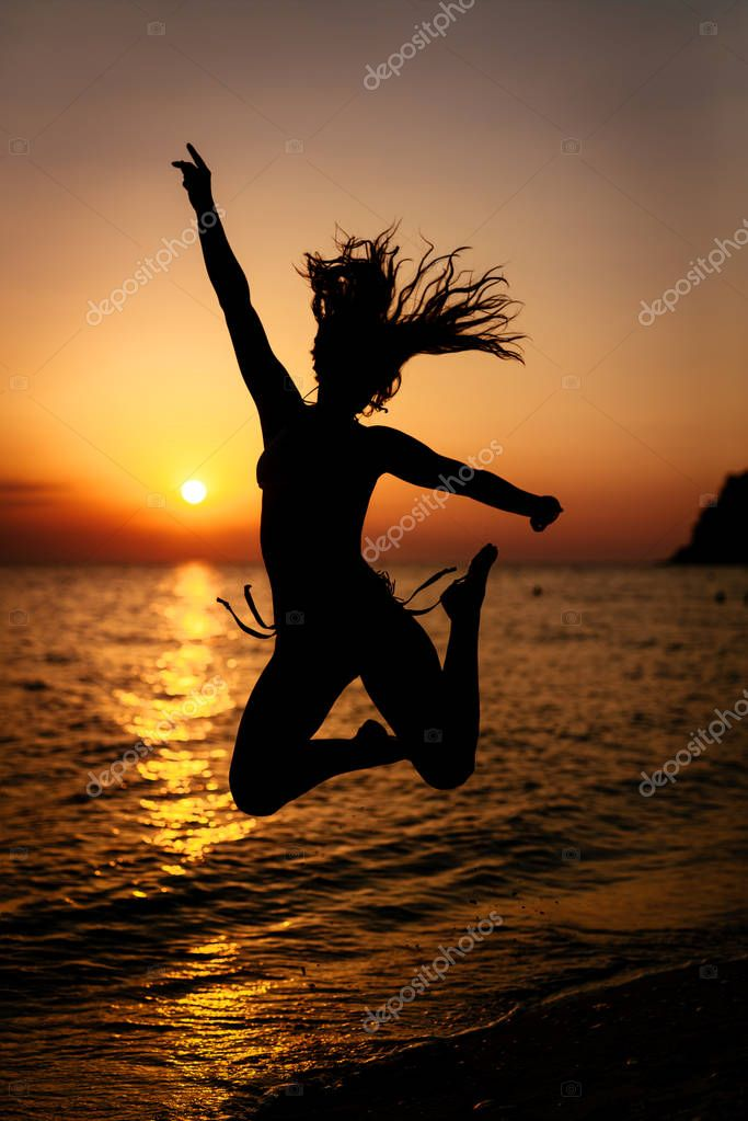 Silhouette of  happy girl jumping at sunset on the beach